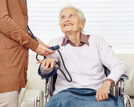 Nurse measuring blood pressure for senior woman in wheelchair in a nursing home photo