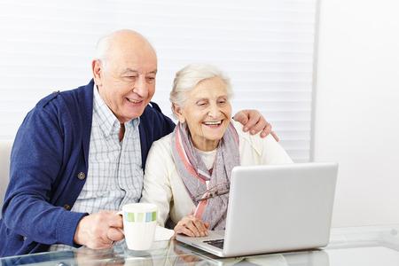 persona de la tercera edad: Feliz pareja de ancianos utilizando equipo port�til en casa Foto de archivo