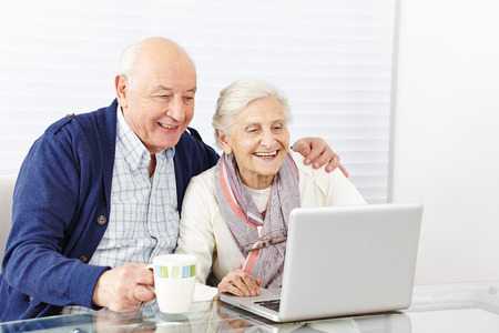 Happy senior citizen couple using laptop computer at home photo