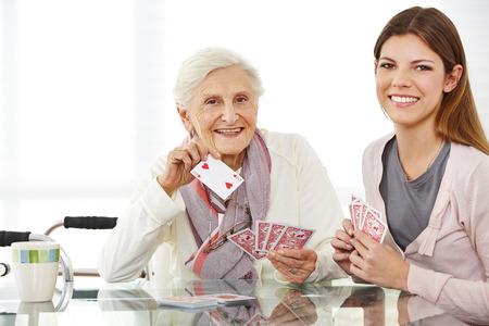 Jonge ouderenzorg verpleegkundige speelkaarten met happy senior vrouw