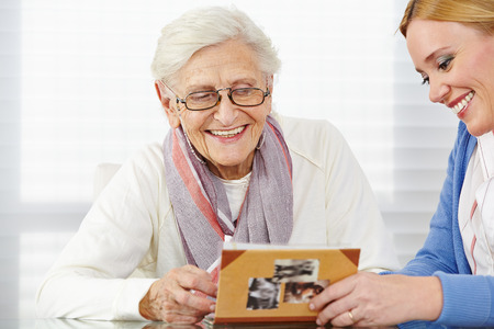 Happy senior vrouw kijken naar foto-album met de ouderenzorg verpleegkundige