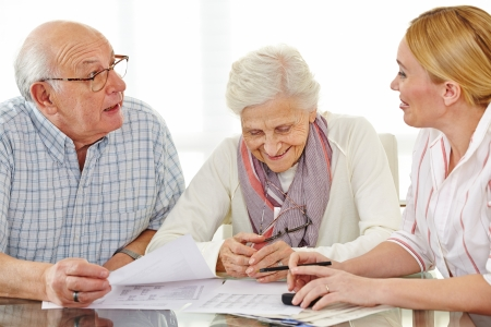 Couple of senior citizens talking to financial consultant about their pension photo