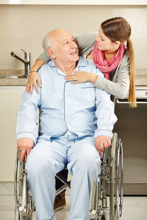 Happy young woman embracing a senior man in wheelchair photo