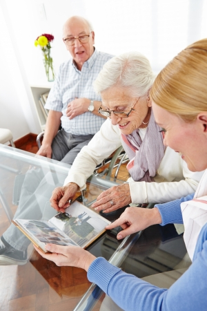 Happy senior woman looking at photos in photo album of her family