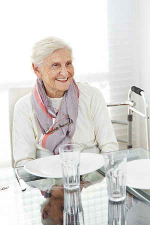 Happy senior woman sitting at set table for lunch photo