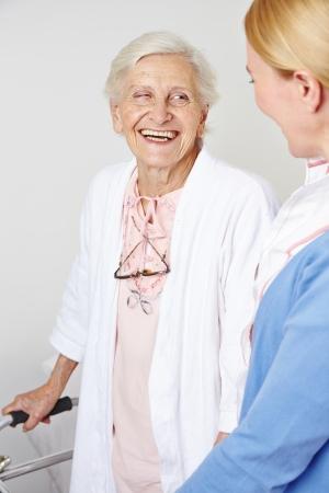 Happy senior citizen woman in nursing home with a nurse photo