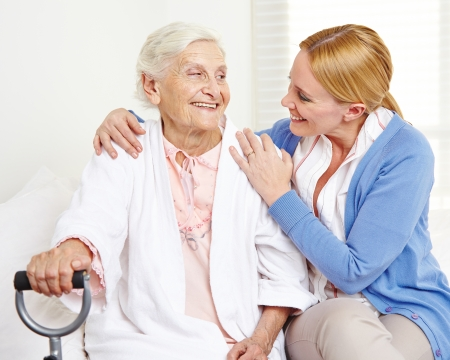 social worker: Happy senior citizen woman at home looking at her daughter