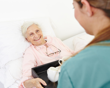 Happy senior woman getting breakfast in bed in a nursing home photo