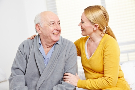 domestic staff: Woman and old senior man in retirement home smiling at each other Stock Photo
