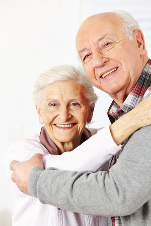 Happy senior citizen couple dancing together and smiling Stock Photo