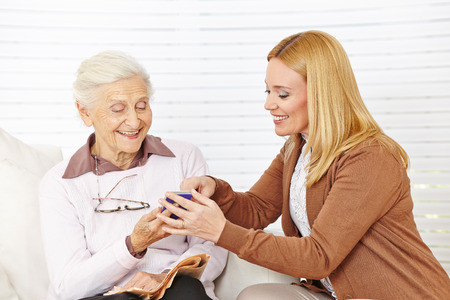 Smiling woman helping senior woman to use her smartphone photo