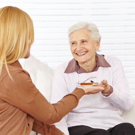 Old happy woman eating breakfast in a nursing home photo