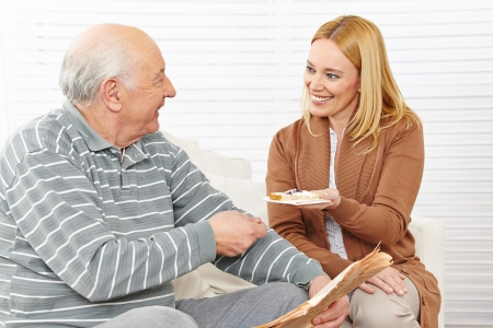 assisted living: Senior citizen and woman eating breakfast at assisted living home Stock Photo