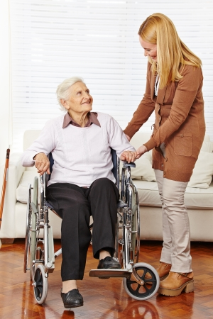 Caregiver helping senior citizen woman in a wheelchair at home photo