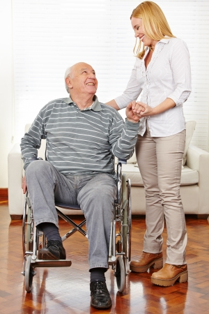Smiling caregiver helping senior citizen man in wheelchair standing up