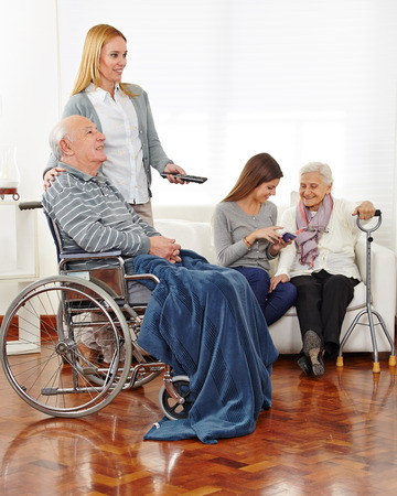 social apartment: Caregiver entertaining senior citizens in a retirement home
