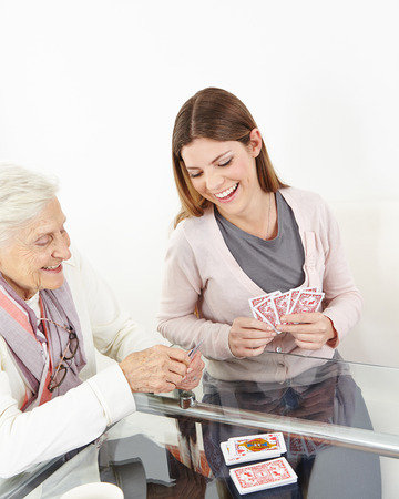 Happy senior woman playing cards with smiling granddaughter at home photo