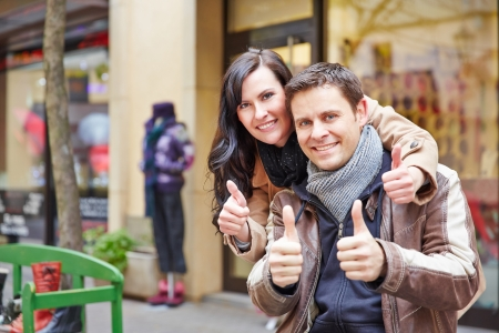 acknowledgment: Happy couple in Berlin city holding their thumbs up Stock Photo
