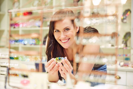 Smiling woman shopping for bangle in a jewelry store photo