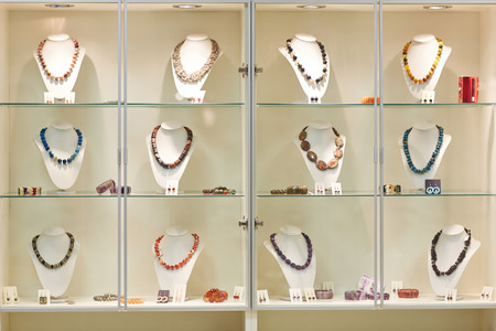 Different necklaces on display in jewelry store window photo