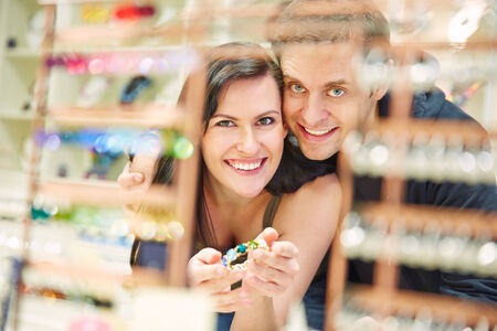Happy couple shopping for bangle at jewelry store photo
