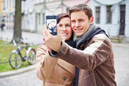 Happy couple taking self portrait with smartphone in an autumn city photo