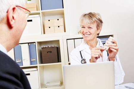 doctor giving pills: Elderly doctor giving pills to senior man in her office