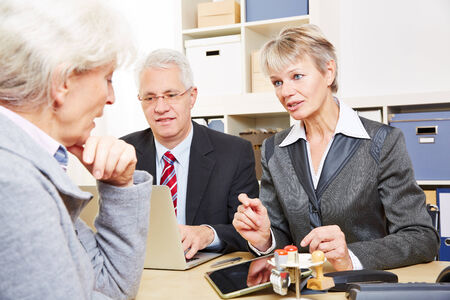 Elderly senior woman at communication over financial issues in a bank photo