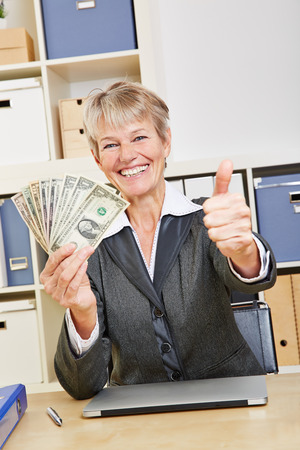 winning business woman: Happy winning business woman holding dollar bills and thumbs up Stock Photo