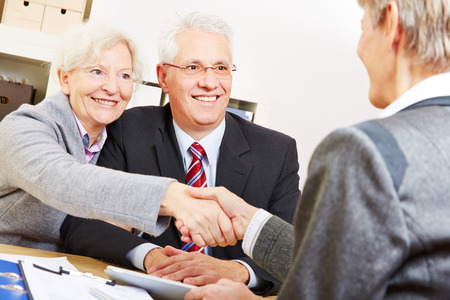 Happy elderly couple shaking hands with legal consultant in law firm photo