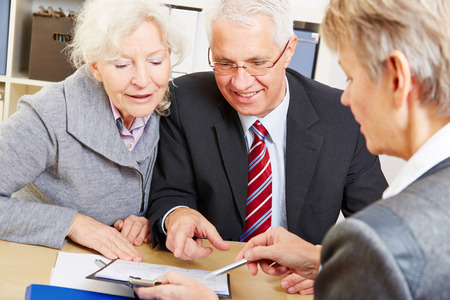 old office: Senior couple writing signature under contract after financial consultation