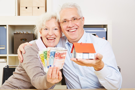 Happy elderly couple with fan of Euro money and little house in their hands photo