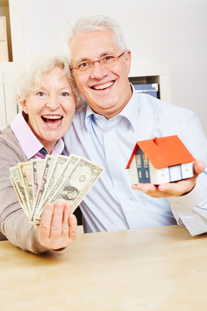Happy elderly family with dollar bills and a small house photo
