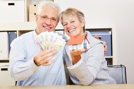 Happy elderly couple with a little house and Euro money in their hands photo