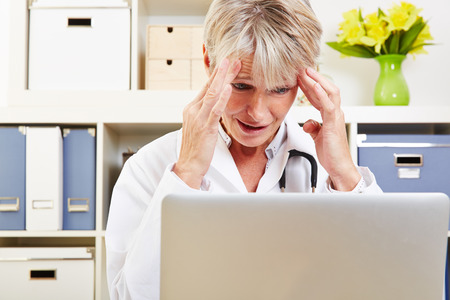 doctor burnout: Elderly female doctor with burnout syndrome in her office at the desk Stock Photo