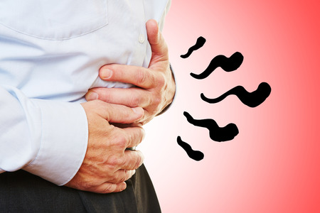 Man with abdominal pain in stomach holding hands on his belly photo