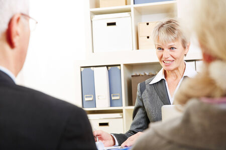 financial issues: Senior couple taking with bank consultant about financial issues Stock Photo