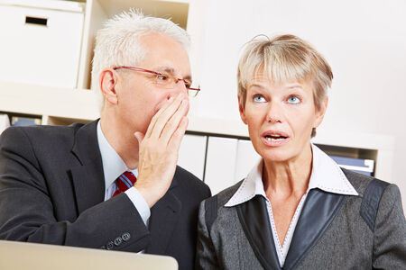 Business man in the office whispering a secret into ear of surprised woman photo