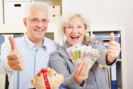 Happy senior couple with fan of Euro money holding thumbs up photo