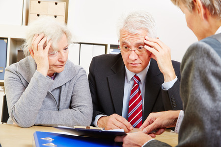 pensions: Anxious elderly senior couple worring about financial security at consultation Stock Photo