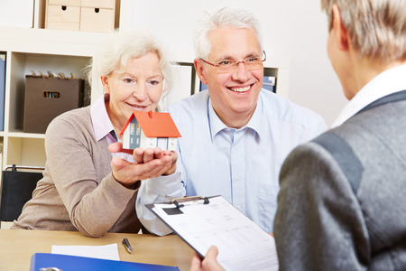 residential home: Happy senior couple with little house buying real eastate in office