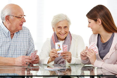 Happy senior couple playing cards with young woman