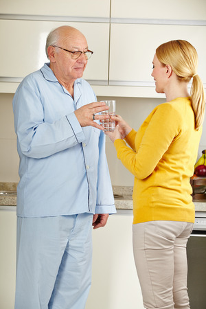 Woman offering a senior man a glass of water in the kitchen Stock Photo