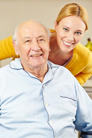 nursing treatment: La mujer y el hombre en la silla de ruedas sonriendo juntos