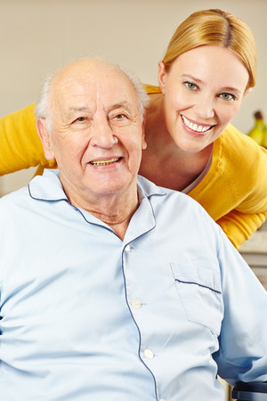 social work aged care: Woman and old man in wheelchair smiling together Stock Photo