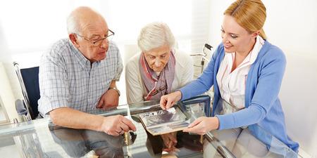 高齢者のカップルが彼らの娘と一緒に写真アルバムを見て