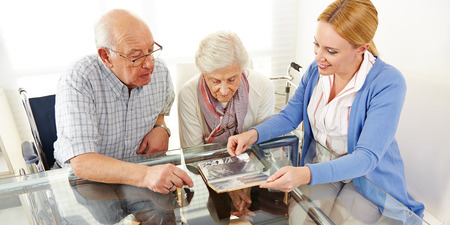 pensioners: Senior citizens couple watching a photo album with their daughter Stock Photo