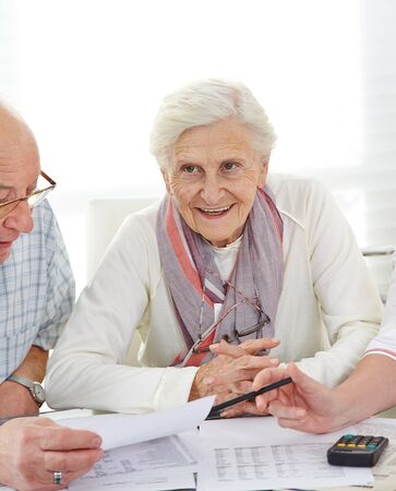 Senior couple discussing their financial situation with bills on the table photo
