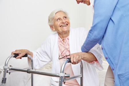 levantandose: Enfermera que ayuda a los pacientes de la tercera edad en el hogar de ancianos de levantarse Foto de archivo