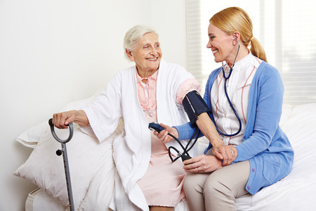 Geriatric nurse measuring blood pressure of senior citizen woman in nursing home Stock Photo